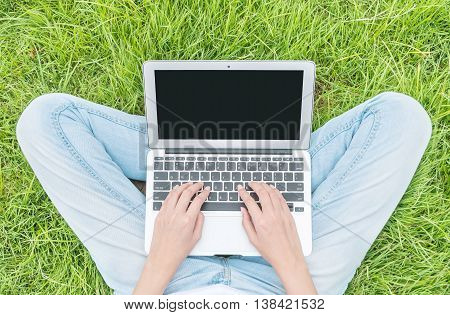 Asian woman sitting on grass floor in the garden textured background for use a notebook computer work concept at the outdoor