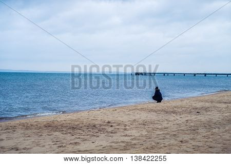 a lone woman looking sadly over the sea and cliffs edge in county