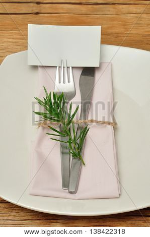 A simple place setting consisting of a plate and a knife and fork with a napkin that is tied together an empty name card and a piece of a plant