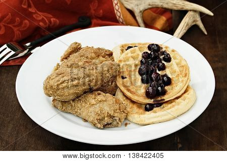 Three pieces of deep fried chicken with waffles served with fresh blueberry sauce over a rustic background. Extreme shallow depth of field.