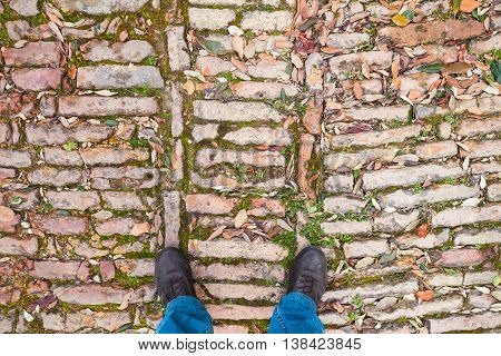 Male Feet In Shoes Stand On Old Cobblestone