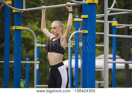 Sporty girl pulled on the bar in a sports suit