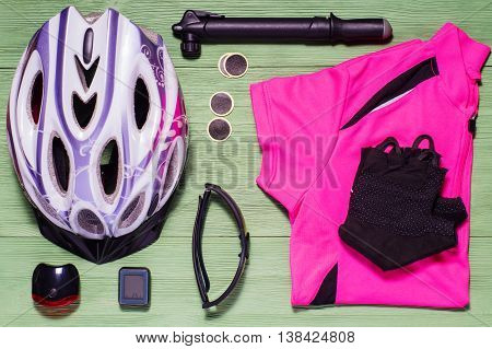 Items replacements and tools for a safe cycling: Helmet shirt gloves glasses pump patches, flat lay. Tools and accessories set for cycling flat lay. Sport equipment sports uniform, top view.