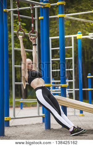 Beautiful girl in a tracksuit on the Playground deals with rings