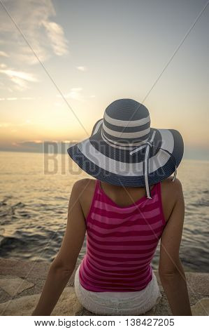 Rear view on person in pink sleeveless top and wide brim hat sitting on rock near water in front of setting or rising sun.