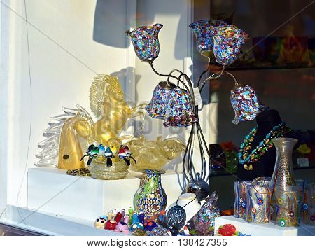MURANO ITALY - SEP 25 2014: Glass goods from murano glasses displayed in a shop window. Today Murano is home to a vast number of factories making all manner of glass objects