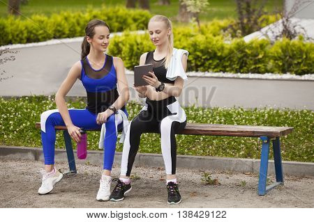 Two sports girls during a break looking at the tablet