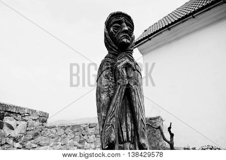 Wooden Statue Of Old Sad Praying Woman. Black And White
