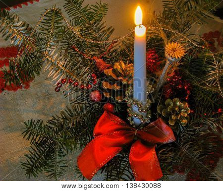 Christmas arrangement with lit candle and pine cones