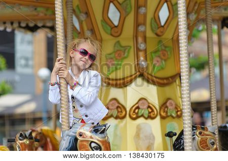 Child On Old French carousel in a holiday park. Elegant Charming cute little girl in fashionable clothes and sunglasses enjoys, sitting on carousel horse. Looking to the side.