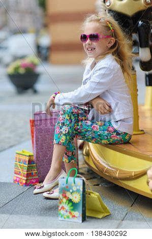 Child On Old French carousel in a holiday park. Elegant Charming cute little girl in fashionable clothes and sunglasses enjoys, sitting with full shopping bags. Looking to side.