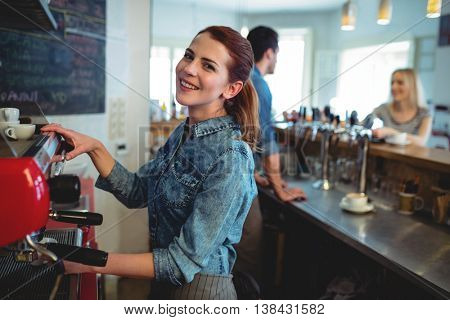 Portrait of happy waitress with co-worker talking to young female customer at coffee shop