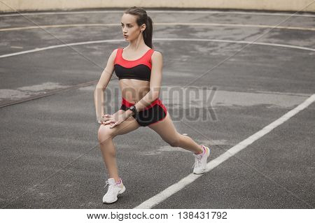 Sexy and sporty girl warming up before a race