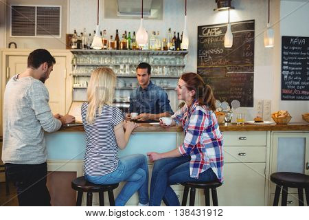 Waiter looking at happy female customers sitting at counter in cafe