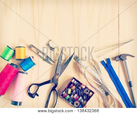 Vintage Background with sewing tools and colored tape/Sewing kit. Scissors bobbins with thread and needles on the old wooden background