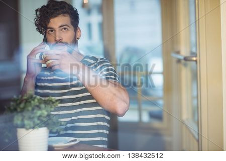 Young man sipping coffee while talking on cellphone at cafe