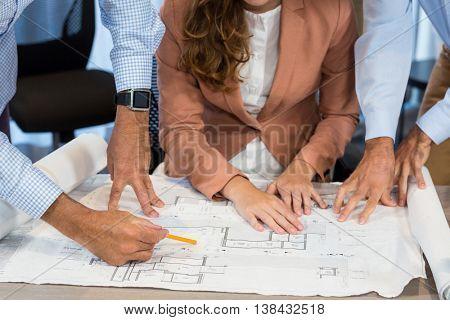 Mid section of businesswoman and coworker discussing blueprint on the desk in the office