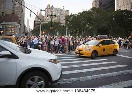 NEW YORK-JULY 12, 2016: A large crowd of people take photos of ManhattanHenge on 23rd St for the event when the setting sun aligns with the city street grid directly between buildings on July 12 2016.
