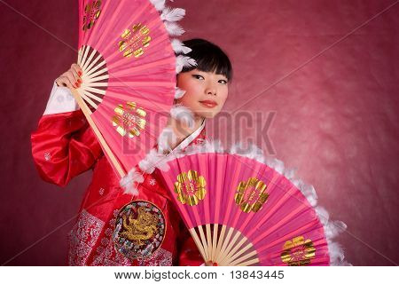 Asian Woman In Traditional Dress With The Fan