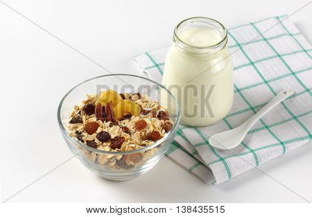 bowl of oat flakes and glass of white yogurt on checkered dishtowel