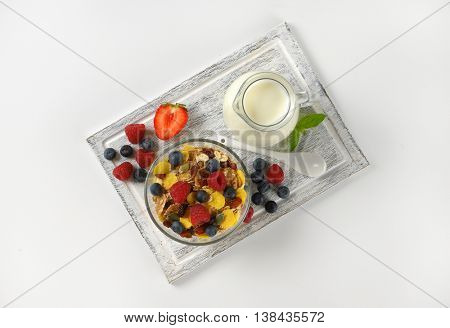 bowl of cereals and berry fruit with milk jug of milk on wooden cutting board
