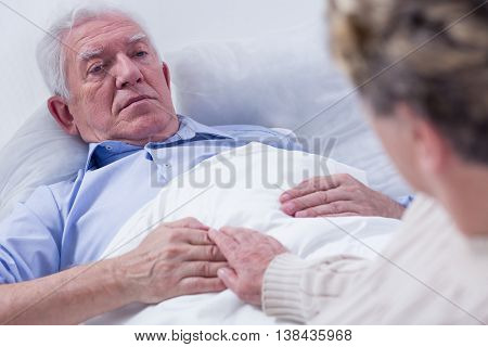 Close-up of a dying elderly man in a hospital bed holding his wife's hand