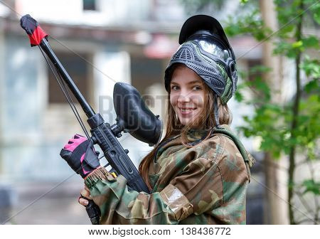 Beautiful girl posing in paintball ammunition outdoors