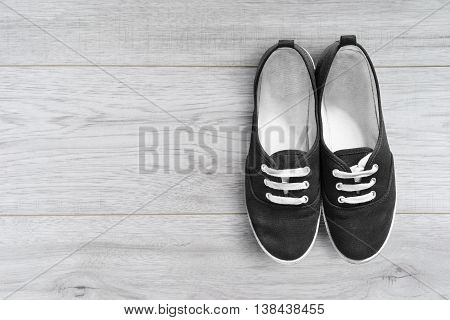 Black gumshoes on white wooden floor as a background