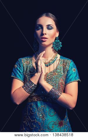 Fine art portrait of beautiful fashion Indian woman with oriental dress, accessories and mehndi henna tattoos with hands clasped and eyes closed enjoying