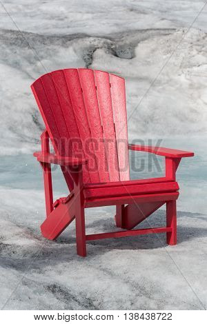 Empty Red Chair Sitting on Glacier with a stream of snow melt behind