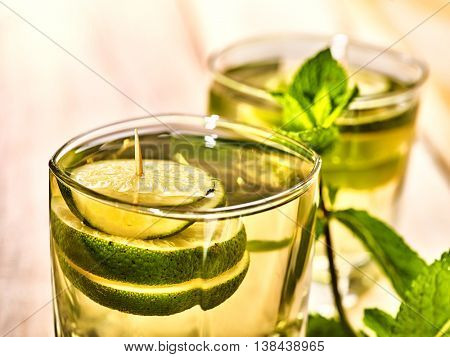 Alcohol drink. On wooden boards are top of two glasses with alcohol green transparent drink. A drink hundred fifty two mojito cocktail with lime and mint leaf . Country life still. Light background.