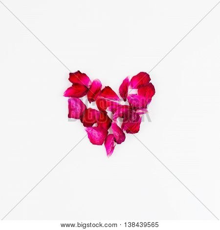 Heart made of rose petals. Tea rose petals heart over white background. Top view with copy space for your text. Love and romantic theme