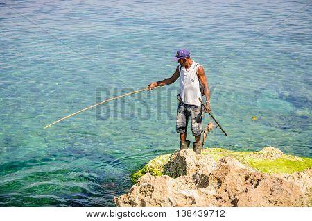 HAVANA, CUBA - MARCH 17, 2016: Fisherman catching octopus in the Malecon in Havana the capital of Cuba