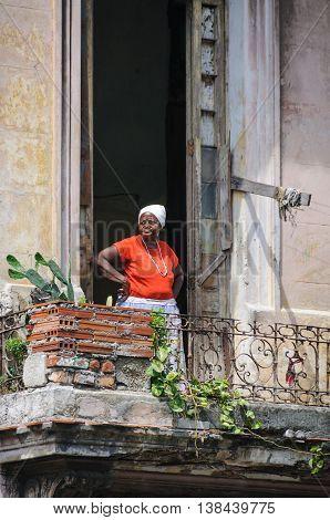 HAVANA, CUBA - MARCH 17, 2016: Woman in a balcony in Paseo de Marti in Havana the capital of Cuba