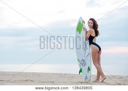 Young sexy girl standing on the beach holding a surfboard