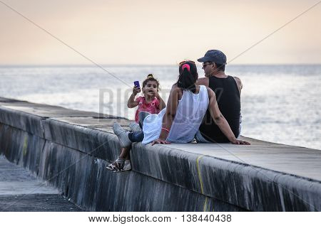 HAVANA, CUBA - MARCH 17, 2016: Family having a calm moment at sunset in the Malecon Avenue in Havana the capital of Cuba
