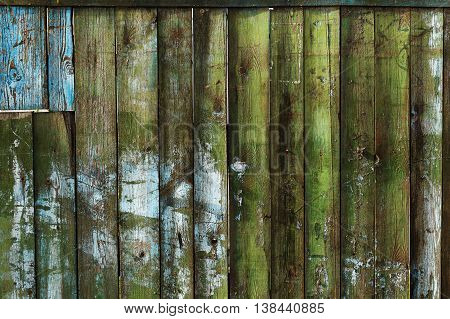 Old shabby wooden broken fence background around construction