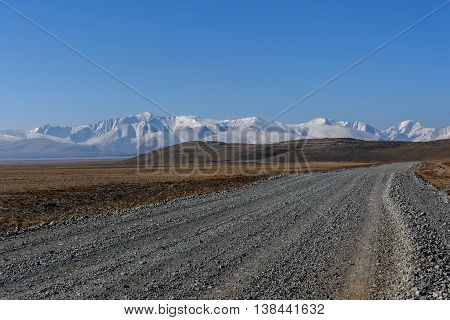 Scenic steppe landscape with a gravel road in the steppe mountains covered with snow and hills against the blue sky on a sunny day