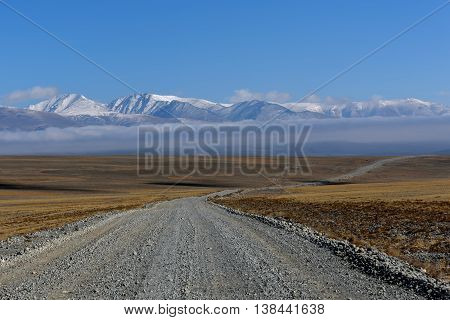Scenic steppe landscape with a gravel road in the steppe mountains covered with snow and the tubular cloud on a background of blue sky and beautiful fluffy clouds