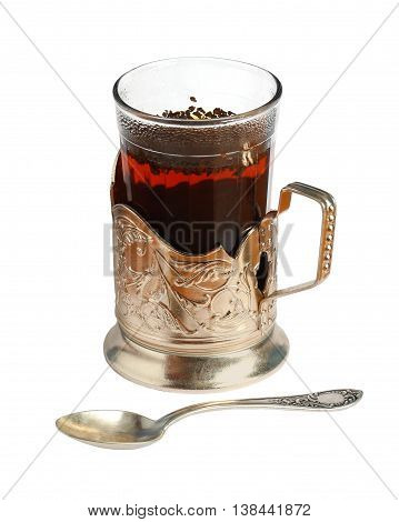Glass of tea in cup holder and spoon. Isolation on a white background