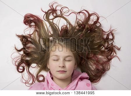 red-haired teenager girl lying on the floor with her hair form a circle.