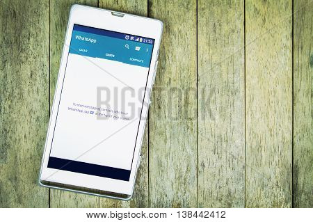 BUNG KAN THAILAND - FEBRUARY 19 2016: smart phone display whatsapp app on wood background space for caption