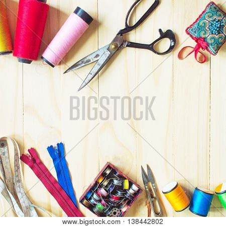 sewing tools and colored tape/Sewing kit. Scissors bobbins with thread and needles on the wooden background