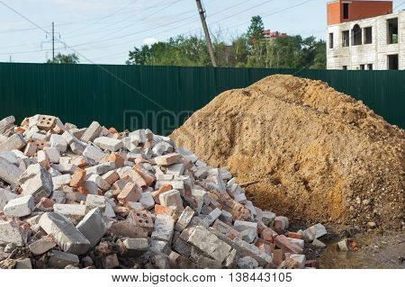 sand and bricks piled near the fence.