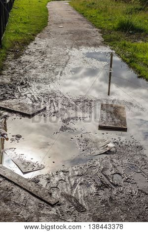 Dirty puddle on a country road with the reflection of sky and clouds.