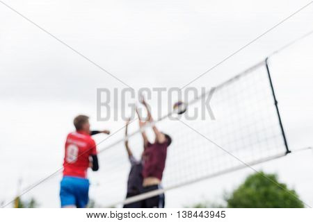 Blurred Volleyball Players Jump To Attack And Block.