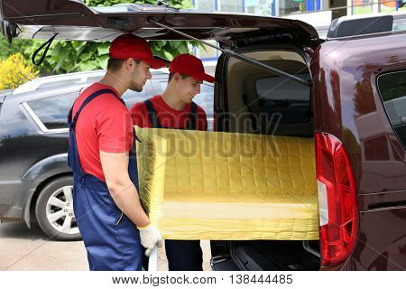 Two male workers unloading yellow couch from car