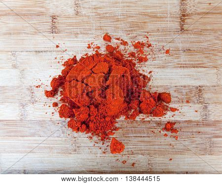 Paprika powder on wooden background of bamboo