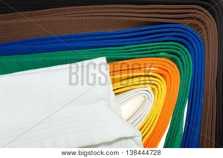 colored belts in martial arts and a part of judo uniform for an almost abstract background