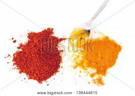 Turmeric (Curcuma) and Paprika powder with spoon isolated on white background.